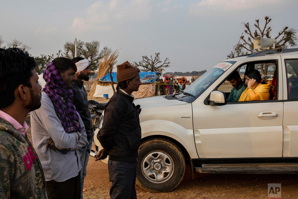 Hindu holy woman Sadhvi Kamal, 40, talks on the phone with members of her vigilante network in front Indian muslim cattle traders on the outskirts of Jaipur, Rajasthan, India, Jan. 25, 2019. (AP Photo/Bernat Armangue)