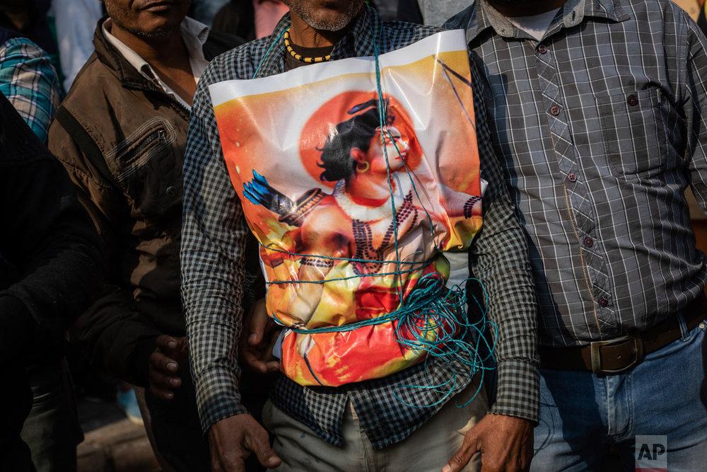 A supporter of Hindu-extreme political group Vishwa Hindu Parishad wears a poster of the Hindu god Ram during a rally in New Delhi, India, Dec. 9, 2018. (AP Photo/Bernat Armangue)