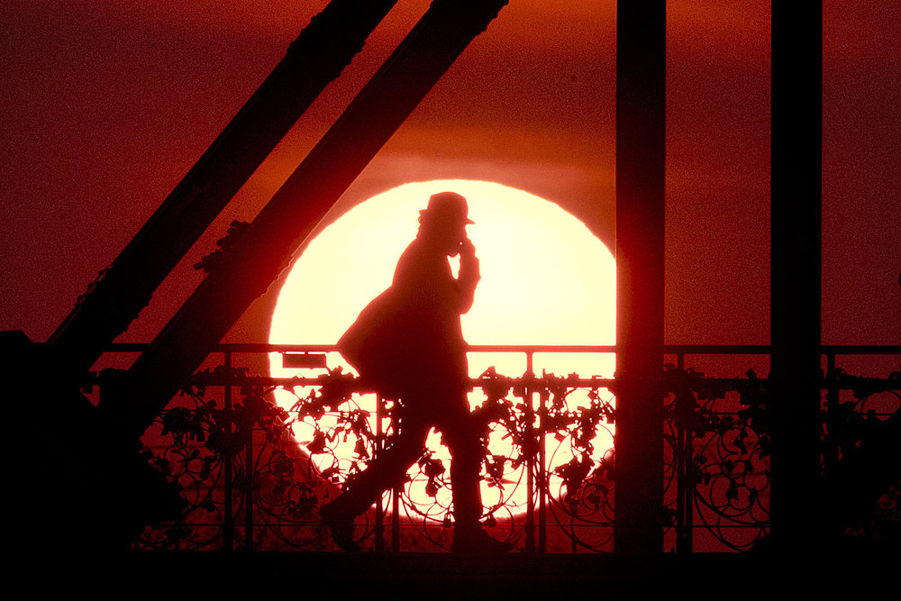 A man walks across the Eiserne Steg (Iron Footbridge) in Frankfurt, Germany, as the sun rises early Tuesday, April 2, 2019. (AP Photo/Michael Probst)