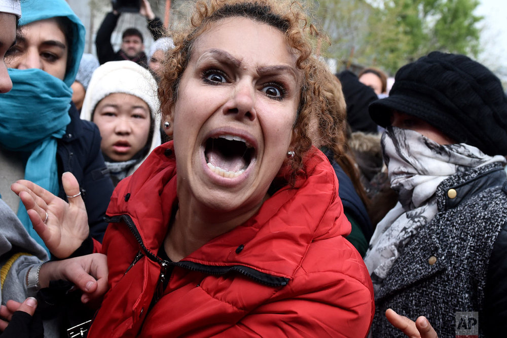 A migrant shouts during a protest outside a refugee camp in the village of Diavata, west of Thessaloniki, northern Greece, Friday, April 5, 2019. (AP Photo/Giannis Papanikos)