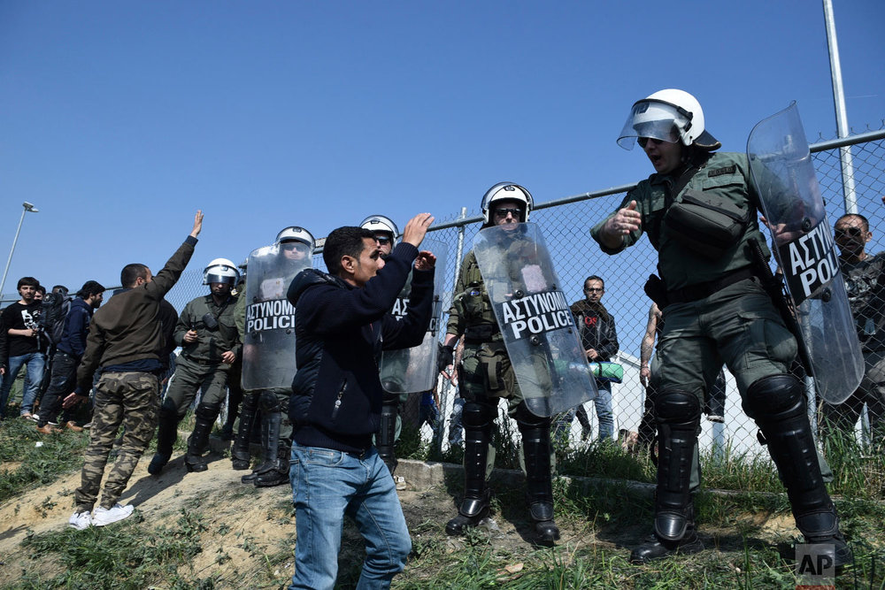 Protesting migrants gather as riot police guard a refugee camp in the village of Diavata, west of Thessaloniki, northern Greece, Thursday, April 4, 2019. (AP Photo/Giannis Papanikos)