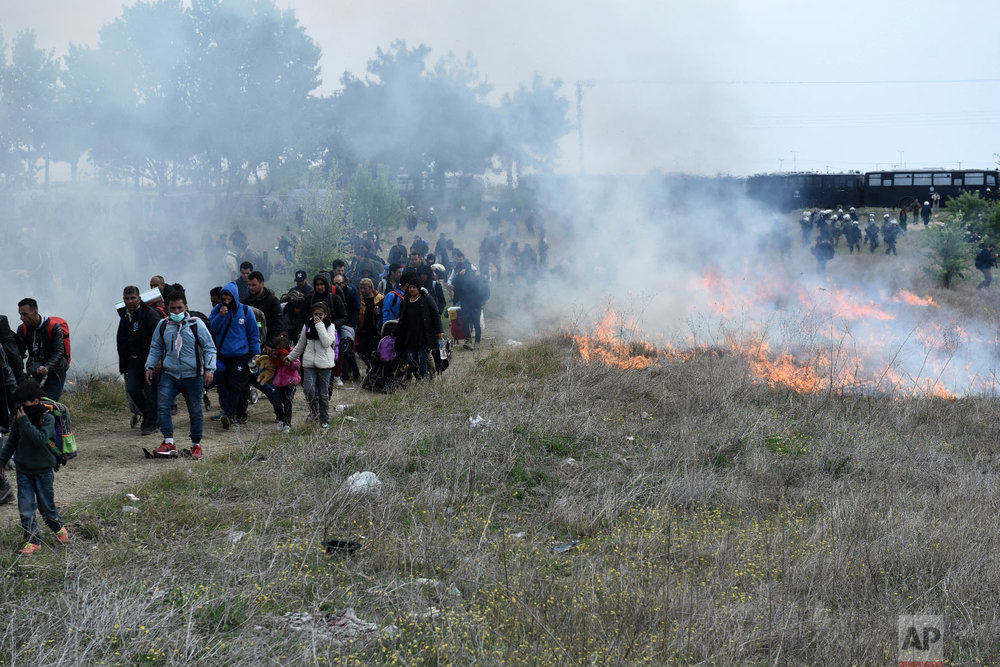 Migrants pass burning long grass during clashes outside a refugee camp in the village of Diavata, west of Thessaloniki, northern Greece, Friday, April 5, 2019. (AP Photo/Giannis Papanikos)