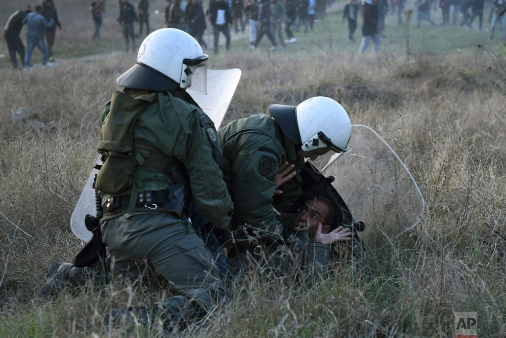 Riot police detain a protesting migrant during a rally outside a refugee camp in the village of Diavata, west of Thessaloniki, northern Greece, Thursday, April 4, 2019. (AP Photo/Giannis Papanikos)