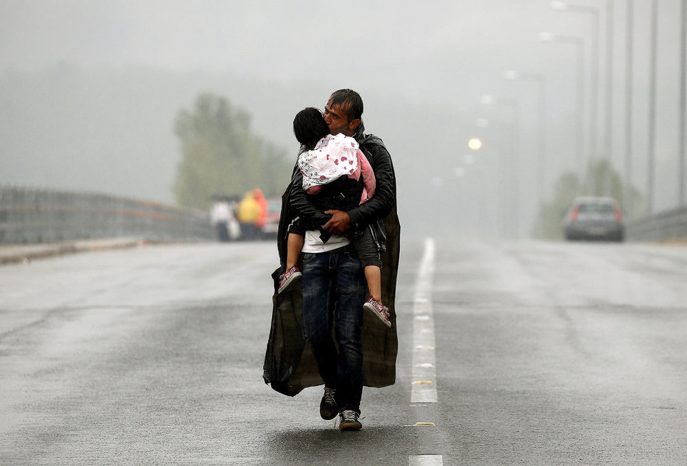 A Syrian refugee kisses his daughter as he walks through a rainstorm towards Greece's border with Macedonia, near the Greek village of Idomeni, September 10, 2015. (REUTERS/Yannis Behrakis)