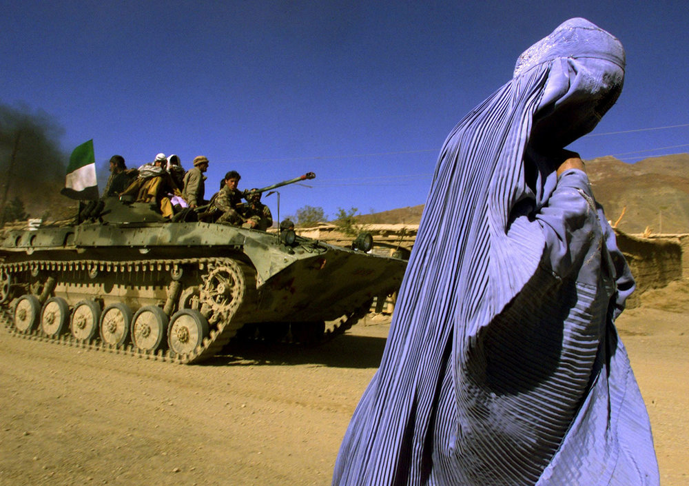 An Afghan woman wearing a traditional Burqa walks on the side of a road as a Northern Alliance APC, (Armored Personnel Carrier) carrying fighters and the Afghan flag, drives to a new position in the outskirts of Jabal us Seraj, some 60kms north of the Afghan capital Kabul, November 4, 2001. (REUTERS/Yannis Behrakis)