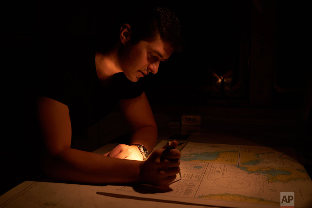 Second officer Konstantin Afanasjev studies the chart of St. Joseph island in the Seychelles during his night watch on board the Ocean Zephyr, April 11, 2019. (AP Photo/David Keyton)