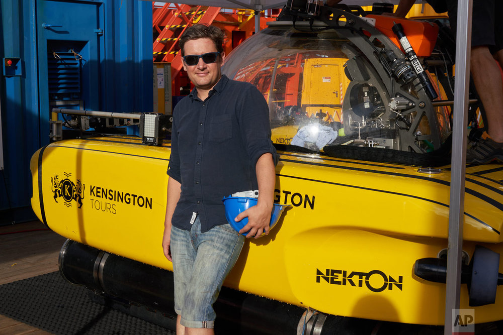 AP Reporter David Keyton stands next to the submersible which took him 400 feet below the surface of the Indian Ocean off the island of St. Joseph, April 8, 2019. (AP Photo/Toby Goode)