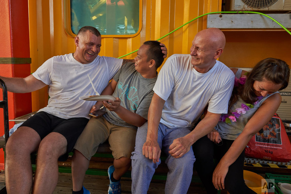A galley crew relax after preparing a barbecue for the researchers onboard the vessel Ocean Zephyr in the waters of the Seychelles, April 2, 2019. (AP Photo/David Keyton)