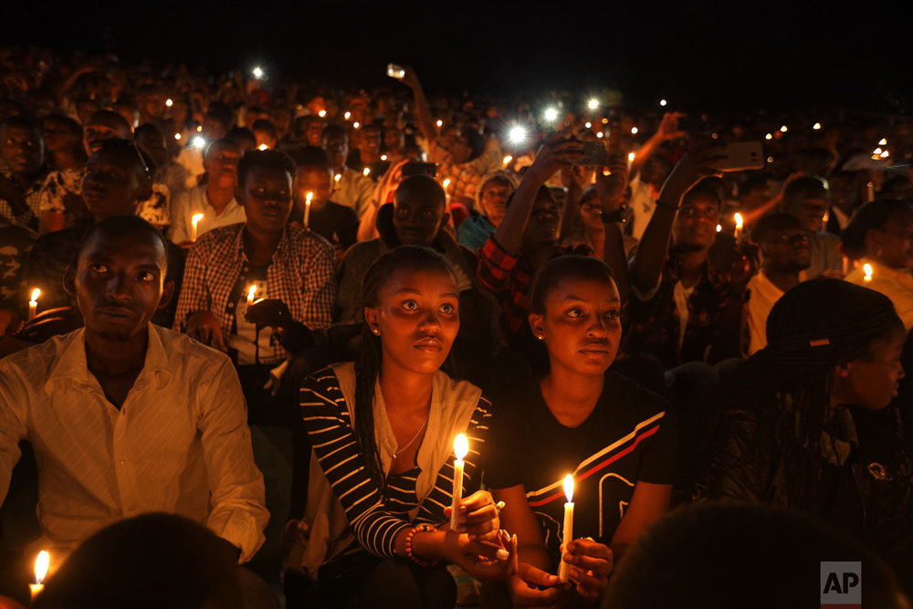 People attend a candlelit vigil during the memorial service held at Amahoro stadium in the capital Kigali, Rwanda, on Sunday, April 7, 2019. Rwanda is marking the 25th year since the country descended into an orgy of violence in which some 800,000 Tutsis and moderate Hutus were massacred by the majority Hutu population over a 100-day period in what was the worst genocide in recent history. (AP Photo/Ben Curtis)