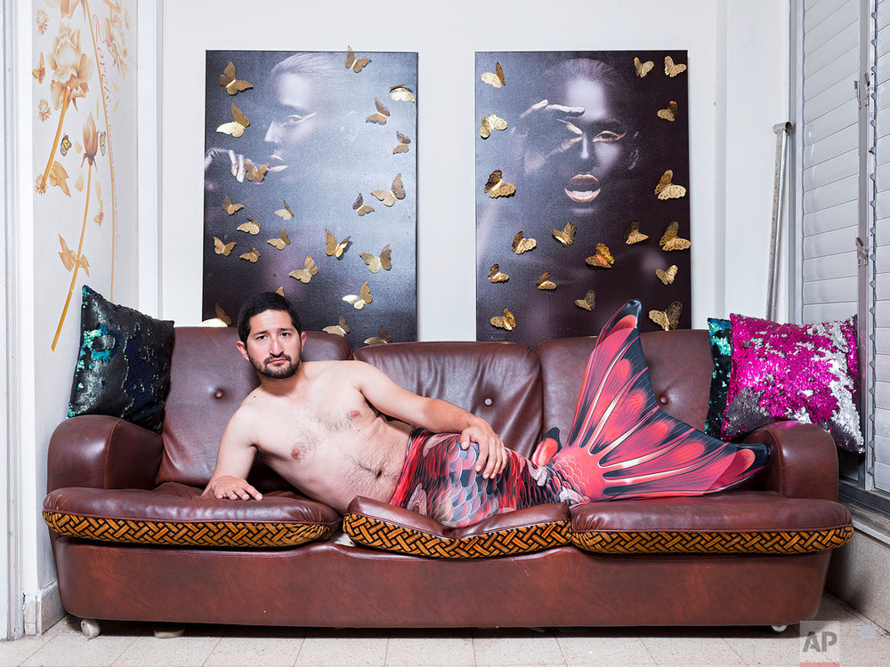 In this Thursday, Feb. 28, 2019 photo, Gal Amnony, a member of the Israeli Mermaid Community, poses for a portrait as he wears a mermaid tail at his home in Ramat Gan, Israel. (AP Photo/Oded Balilty)