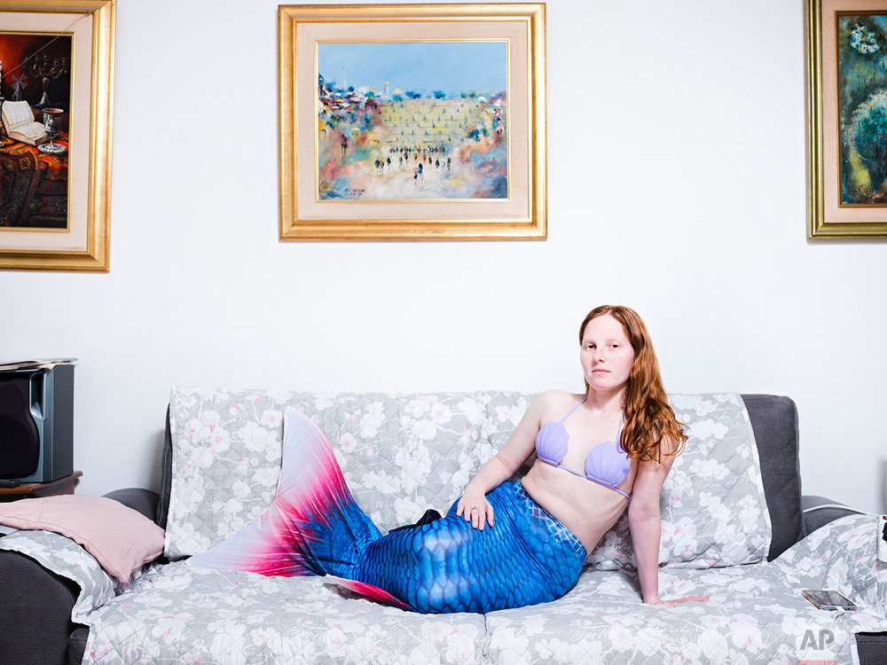 In this Tuesday, March. 26, 2019 photo, Vered Klein, a member of the Israeli Mermaid Community, poses for a portrait as she wears a mermaid tail at her home in Ramat Gan, Israel. (AP Photo/Oded Balilty)
