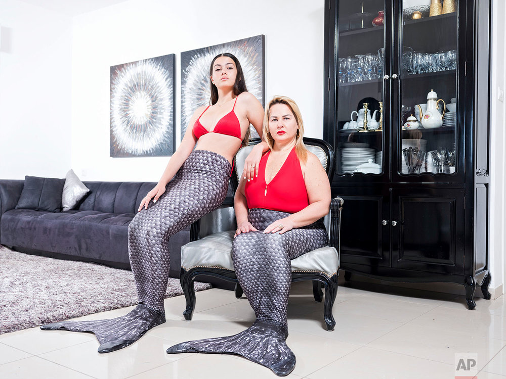 In this Wednesday, March. 6, 2019 photo, Limor Kahlon, right, and her daughter Yam, members of the Israeli Mermaid Community, pose for a portrait as they wear a mermaid tail at their home in Netanya, Israel. (AP Photo/Oded Balilty)
