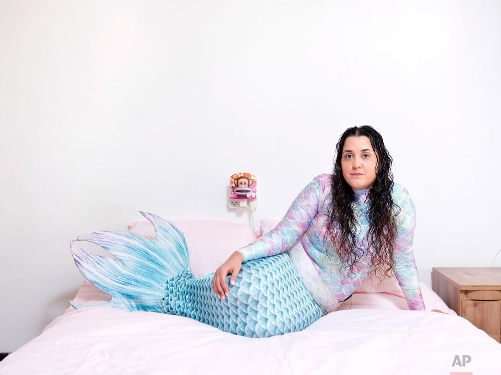 In this Monday, Feb. 18, 2019 photo, Chen Amsalem, a member of the Israeli Mermaid Community, poses for a portrait as she wears a mermaid tail at her home in Bat Yam, Israel. (AP Photo/Oded Balilty)