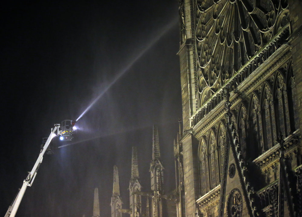 Firefighters spray water onto Notre Dame Cathedral as it burns in Paris, April 15, 2019. (AP Photo/Michel Euler)