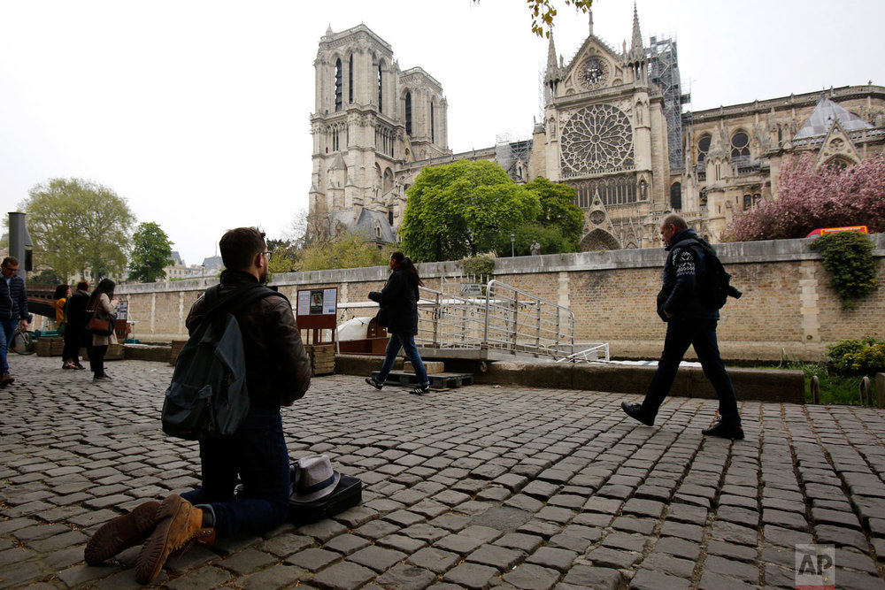 Man kneels as people came to watch and photograph the Notre Dame Cathedral after the fire in Paris, April 16, 2019. (AP Photo/Christophe Ena)
