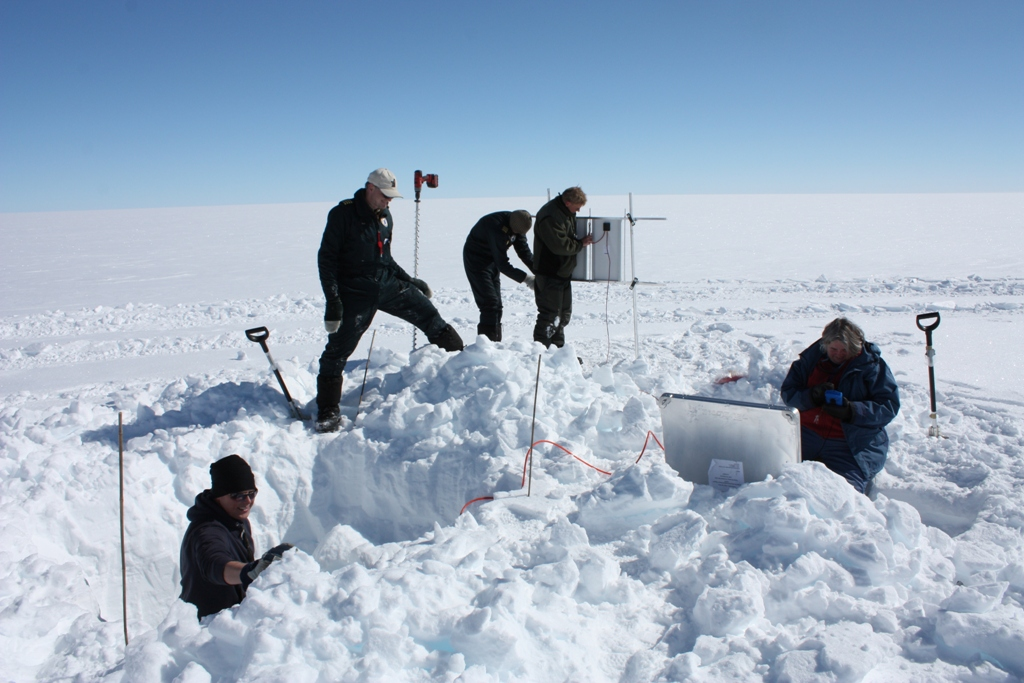 The Dahl-Jensen team installs a seismic station about 200 km from Summit. The station, The team digs a hole into which they place the seismometer, which is stored in the large aluminum box at center right for protection. The team installs a solar panel to charge the batteries powering the datalogger. The prevalence of black clothing seen here is merely a coincidence.