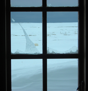 The broken window of the Kinnvika research station at Svalbard. A polar bear, body partially visible in the background, broke the window. Photo: Bob McNabb