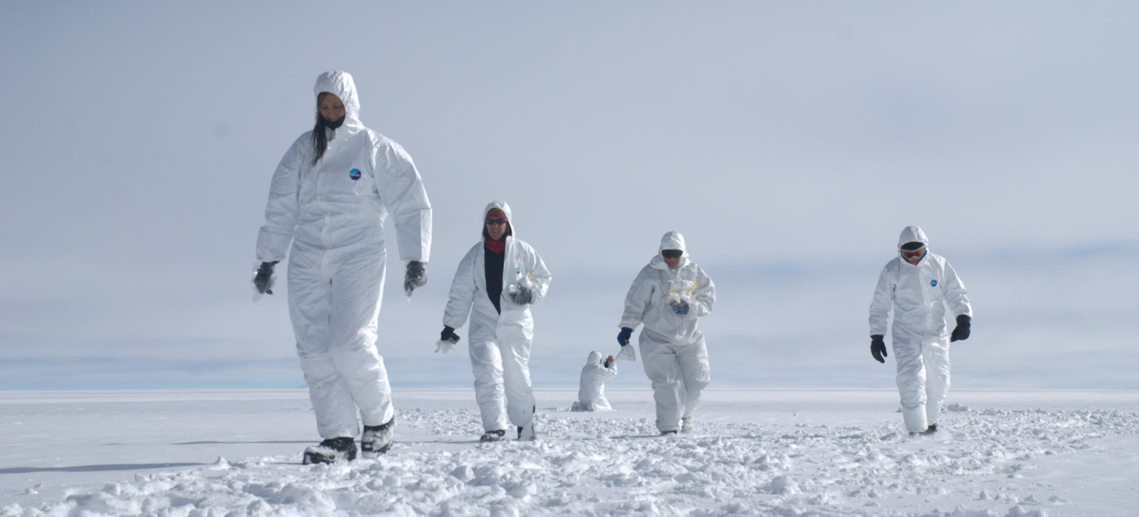 While part of the group collected surface snow samples, donning Tyvek suits to reduce contamination of the snow samples which are analyzed for dust and chemical pollution. . .