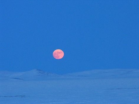 A fat moon climbs over Lake El'gygytgyn in northeast Russia.
