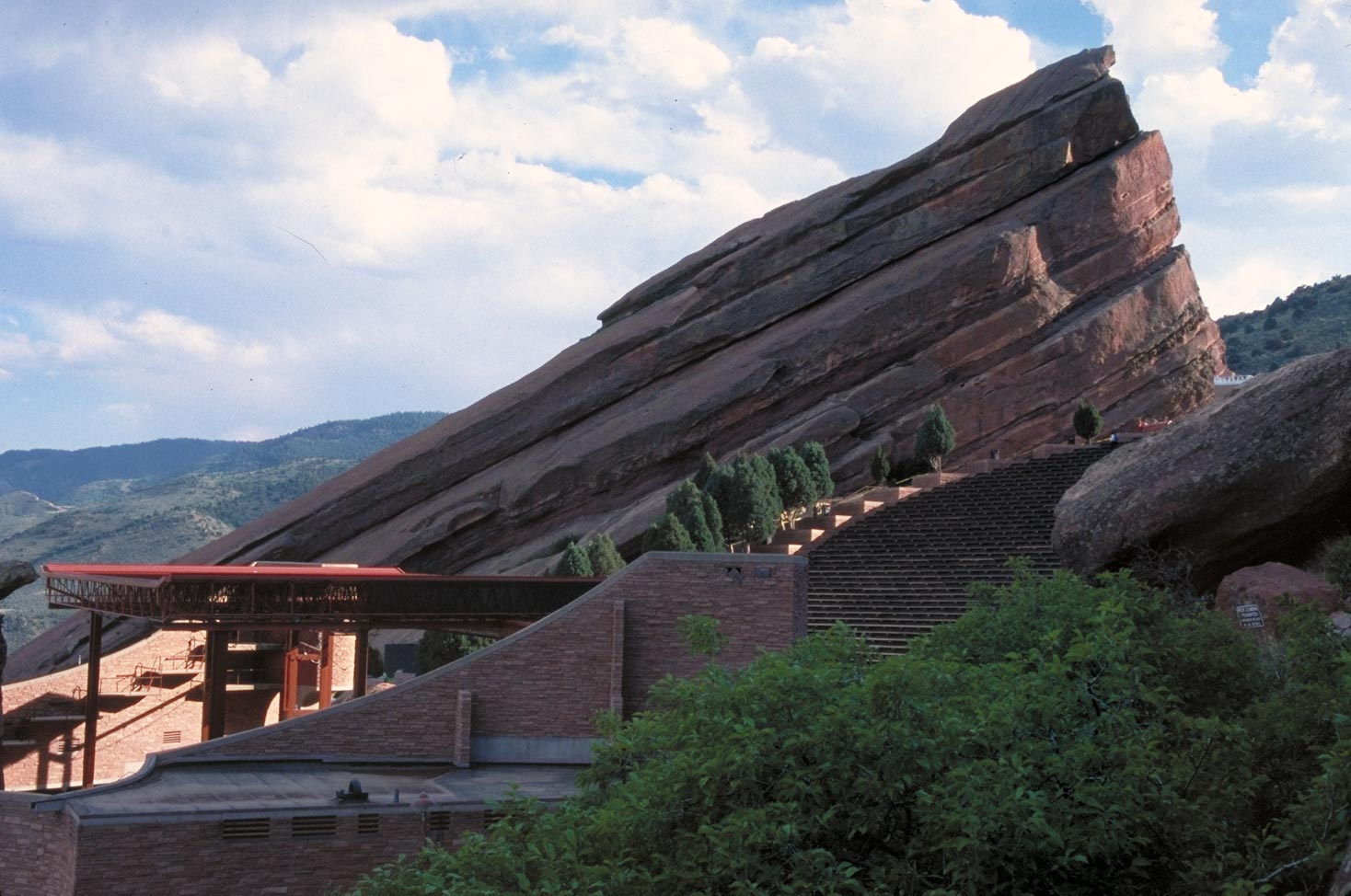 Creation Rock is one of two sandstone monoliths that frame the Red Rocks stage (the structure at left).