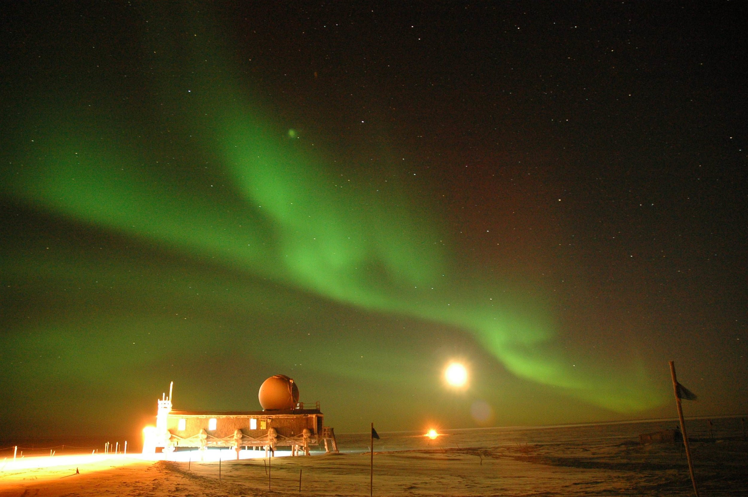 A near-full moon is no match for the aurora borealis, a-light here over Summit Station. Photo: Glenn Grant