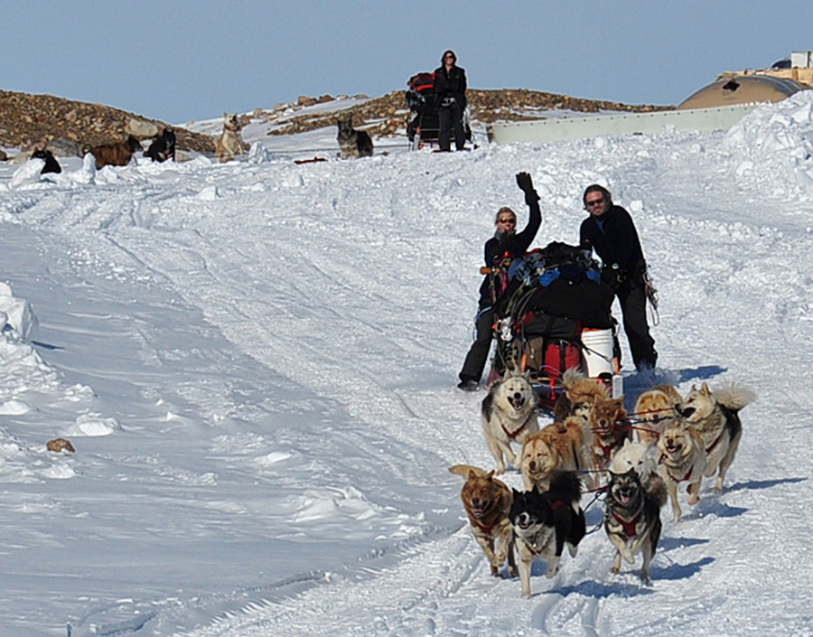 The first team of Polar Huskies pull Mille Porsild, Aaron Doering and the first sled on to the ice sheet, the first few steps of a 1000-mile journey to Summit Station. Photo: Robin Davies
