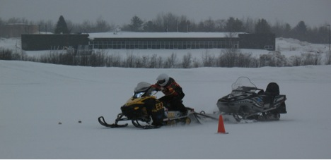 Some events, such as the combined acceleration/load pull shown here, were implemented to better simulate the utility type purposes the ZE sleds are likely to be used for. This is about an 800lb load, not dissimilar to loads that might be encountered at Summit Station. Here the McGill team makes a solid run. The 2kW PV array that offsets the energy used by the ZE teams can be seen in the left middle background.
