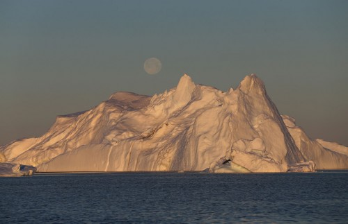 A full moon, over an iceberg from the Jakobshavn Glacier, on July 23, 2013 near Ilulissat. Photo: Joe Raedle/Getty Images
