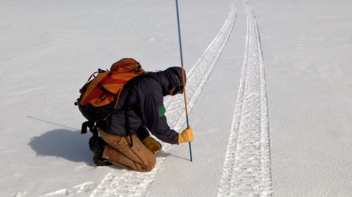 Mark Robertson, a graduate student at Boise State University, checks the depth of the snow pack just after GROVER passes. The pole has graduated markings along its length. Mark is checking the depth of the ice layer formed after the big melt of summer 2012.
