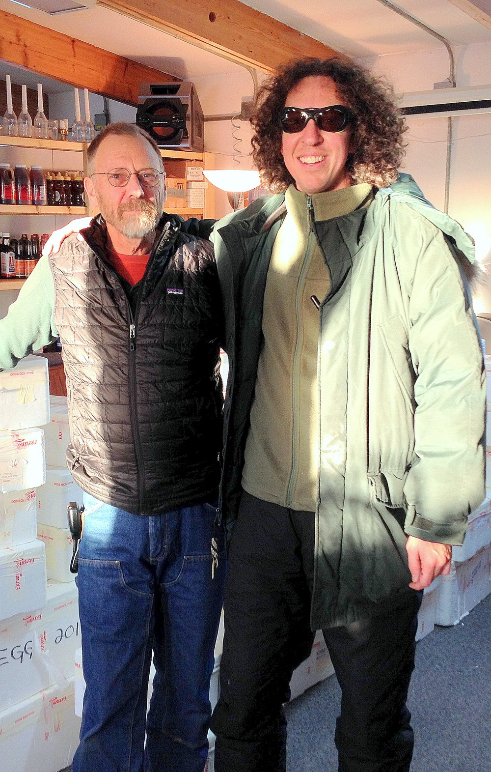 Phil Austin (left) takes the reigns at Summit Station from outgoing manager Brad Whelchel. One of the first tasks for the new five-member staff: unpack and store the freshies that arrived with on the Twin Otter that carried off the departing staff. Photo: Tracy Sheeley