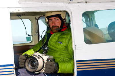 Matt Nolan photographing the Arctic from a plane. Photo courtesy: Matt Nolan