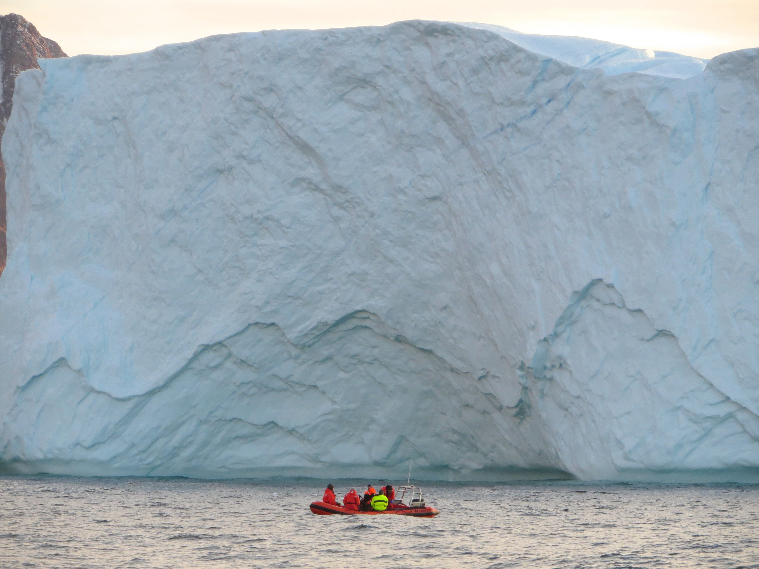 Part of the research involves surveying the conditions at the glacial terminus. Here a team is pictured in front of an iceberg in a Zodiac. Photo: Marcy Davis