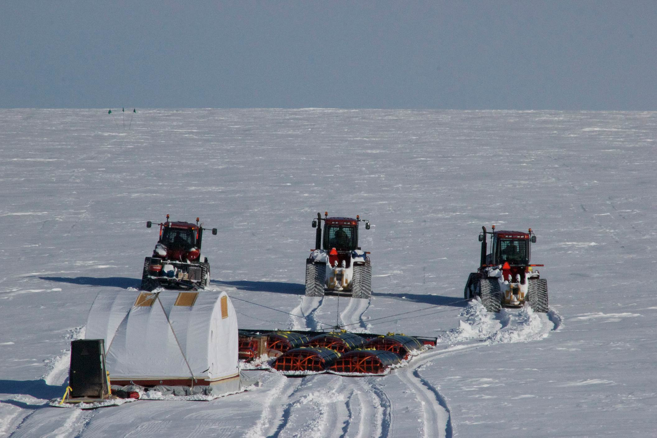 "Three GrIT tractors pull a load of fuel and cargo up the last long hill (called ""Dog Lady Hill"" by the GrIT team) before reaching the ice sheet interior. Photo: Galen Dossin"
