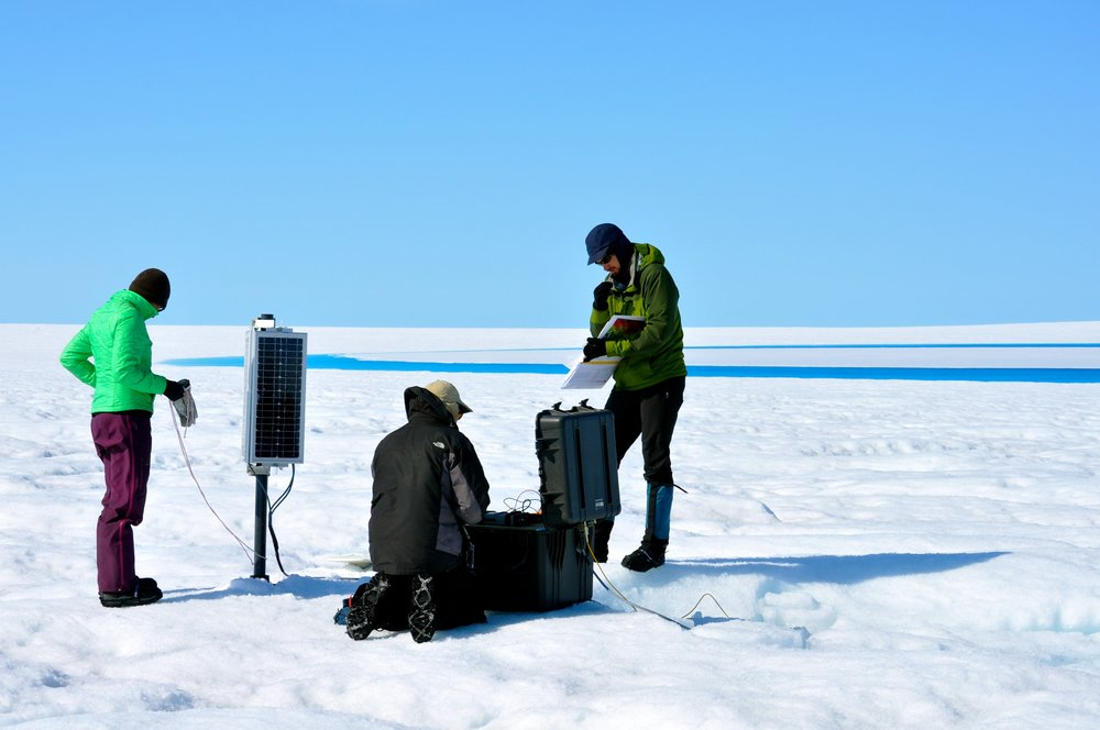 Sarah Das (WHOI), Ian Joughin (UW), and David Shean (UW) service a GPS station in front of a nearby supraglacial lake. Photo: Laura Stevens