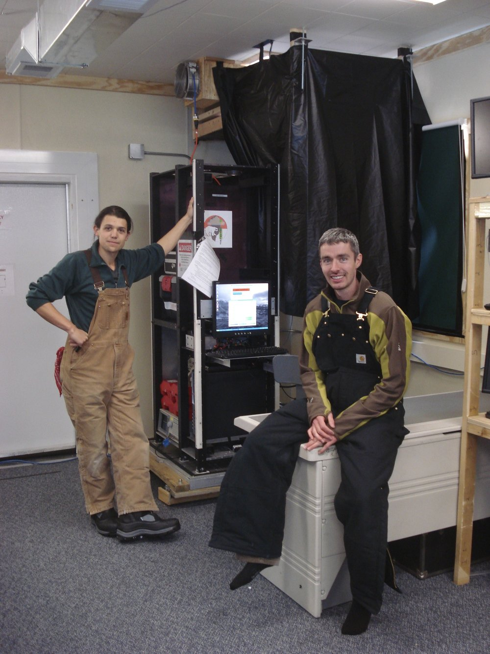 Neely (left) and his student Robert Stillwell (right) next to the LiDAR system, which is stowed behind the black safety curtain. Credit: Ryan Neely