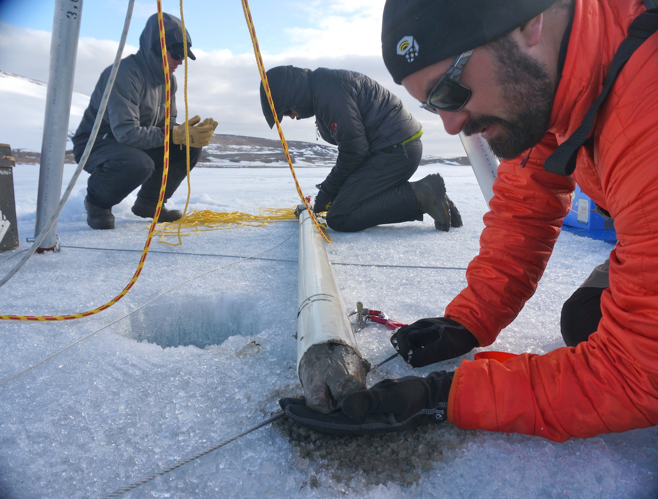 Ryan O'Grady (right), Eric Lutz (center) and Fredrik Eriksson (left) recover a sediment core from a frozen lake during the spring expedition. The small rock at the bottom of the core (in Ryan's hand) suggests that the entire Holocene record was recovered in this 1 m core. Photo: Erich Osterberg.