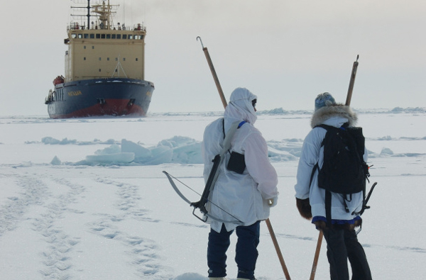 Two people stand on the ice with their testing sticks, hooks visible at the top. The hook could be used to grab onto an article of clothing if someone fell into the water. Photo: Gay Sheffield