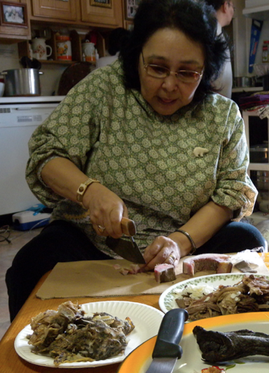 A native woman prepares a meal of fish and walrus in 2011.