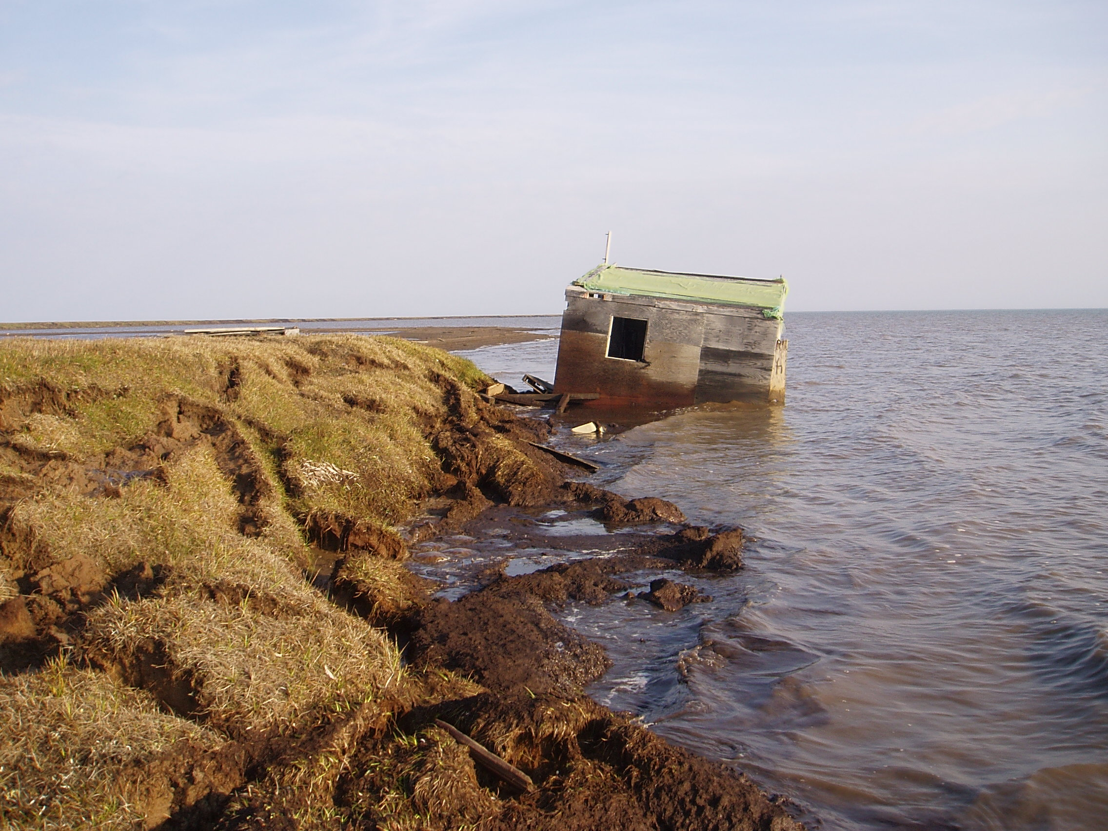 A cabin along the Arctic Alaska coastline was recently washed into the ocean because the bluff it was sitting on top of was eroded away. Photo: Benjamin Jones, USGS