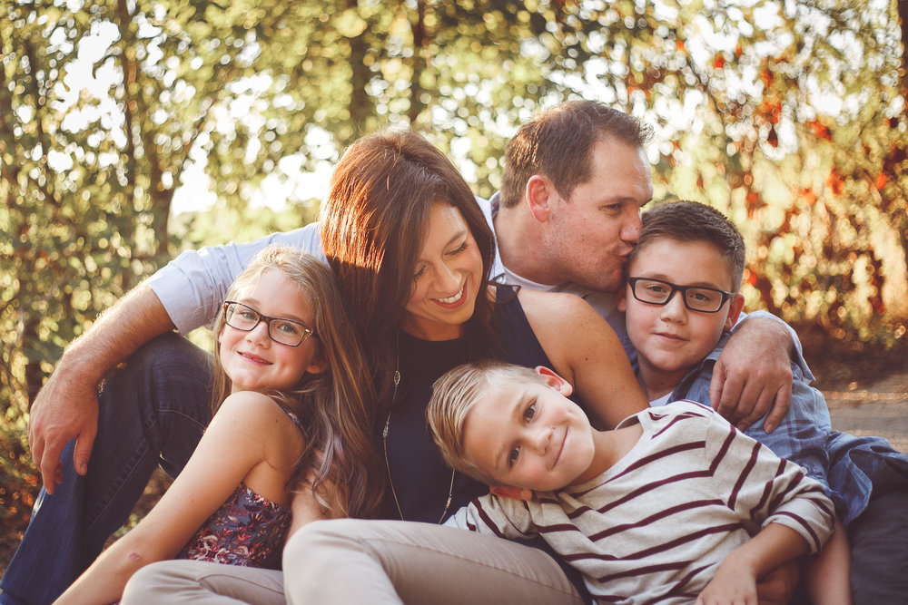 A family of 5 cuddles together and is all smiles with the trees and evening sunshine over their shoulders in a family photograph by L+R Photography