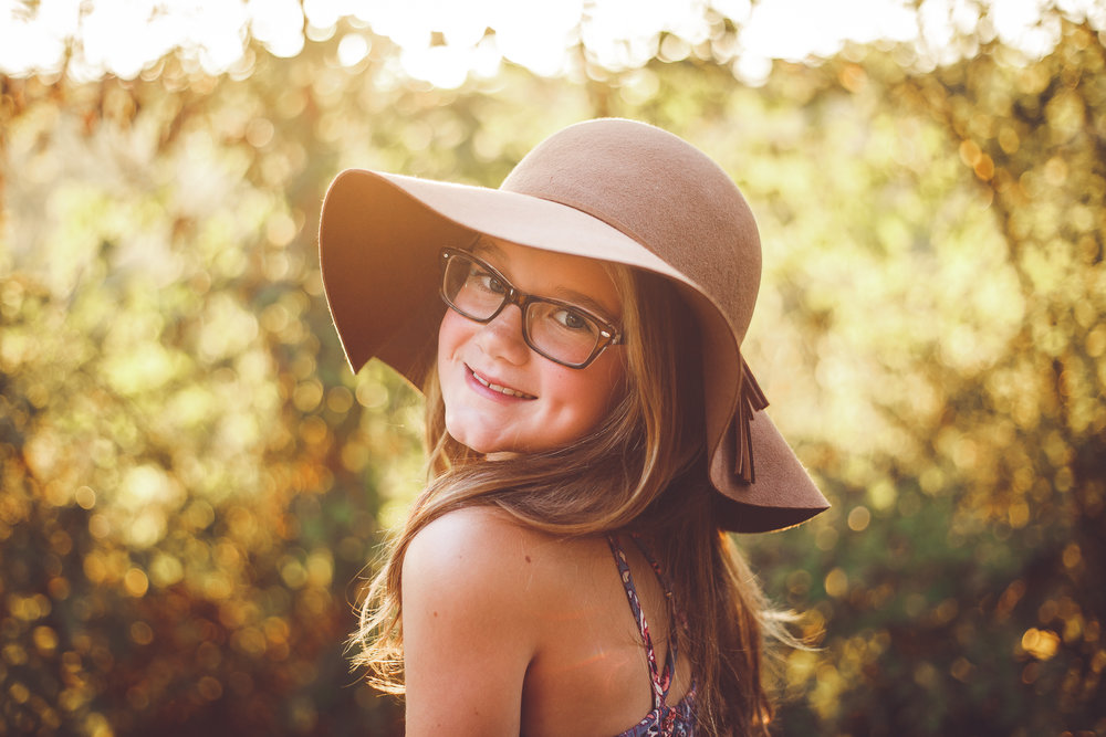 A very cute young girl looks back at the camera and smiles and dimples, wearing a hat in this child photography by L+R Photography from Tulsa , Oklahoma