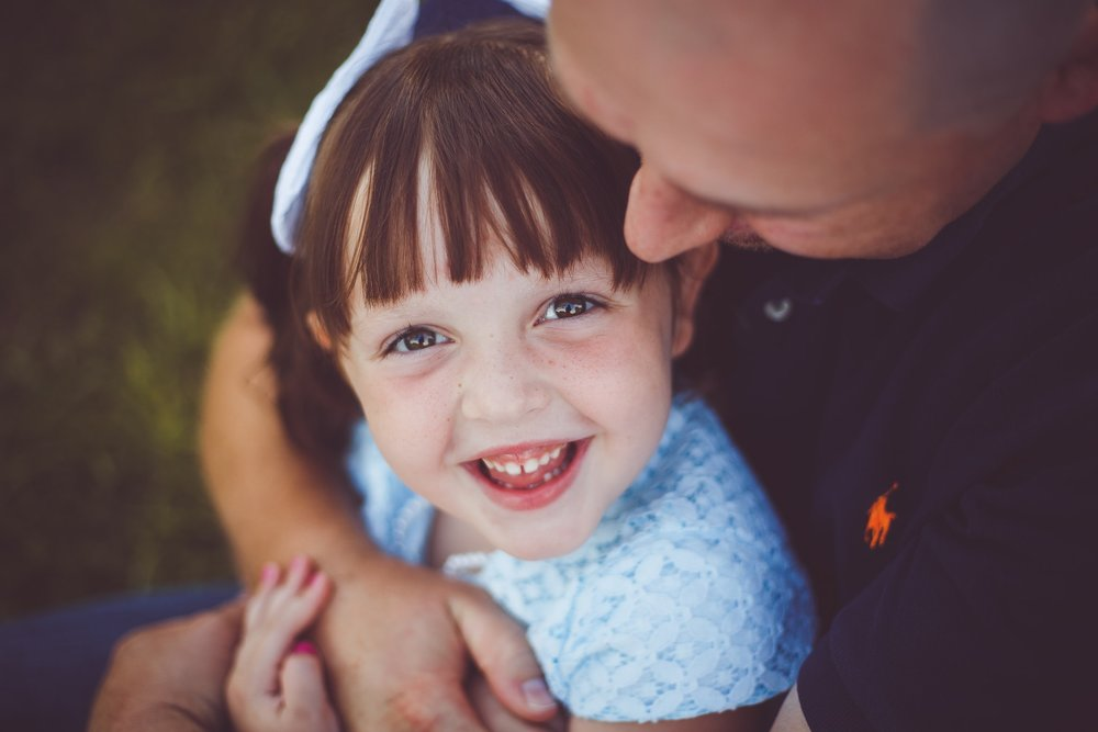 A father holds his daughter in his arms as she looks up and smiles big for the camera - Child Photographer - L+R Photography - Tulsa, Oklahoma