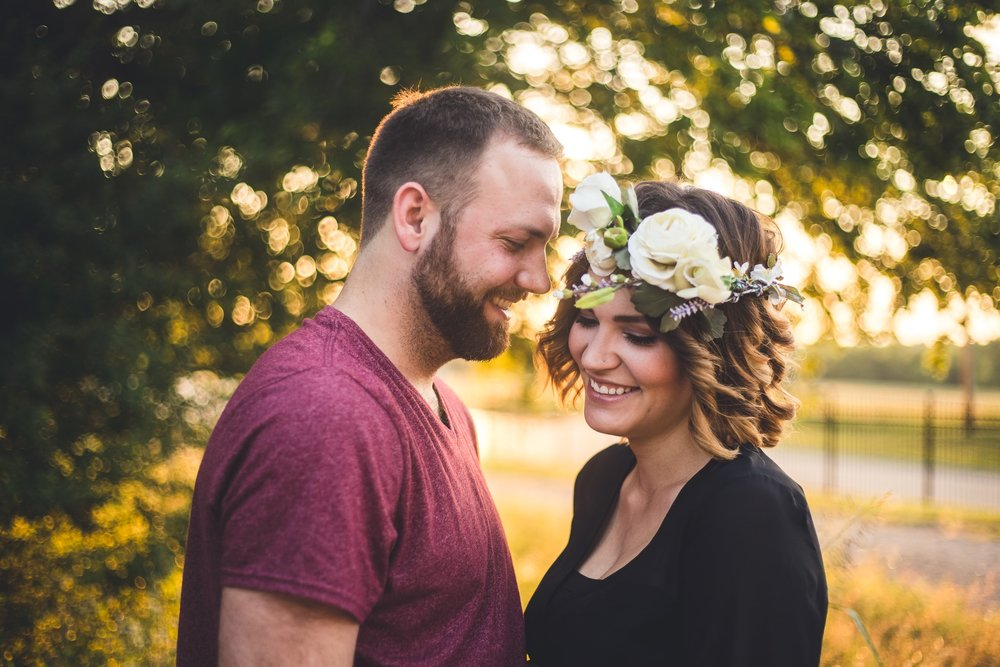 A photograph of a young couple standing facing each other and smiling in this outdoor, natural light couples photography by L+R Photography