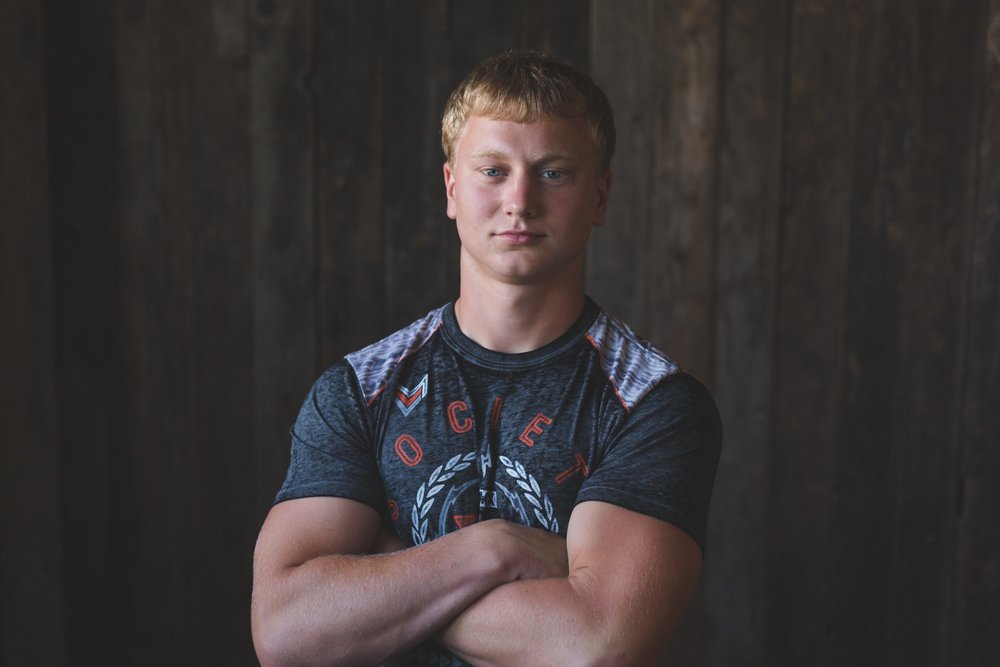 A young senior guy poses for the camera in a t-shirt and in front of a wood background in this senior photography session by L+R Photography - Tulsa , Oklahoma