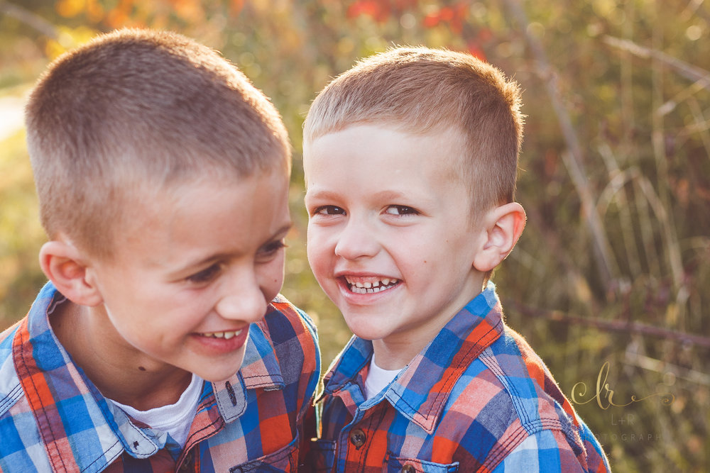 Two young brothers, share a laugh and smile during their family photography session by L&R Photography in Tulsa, OK