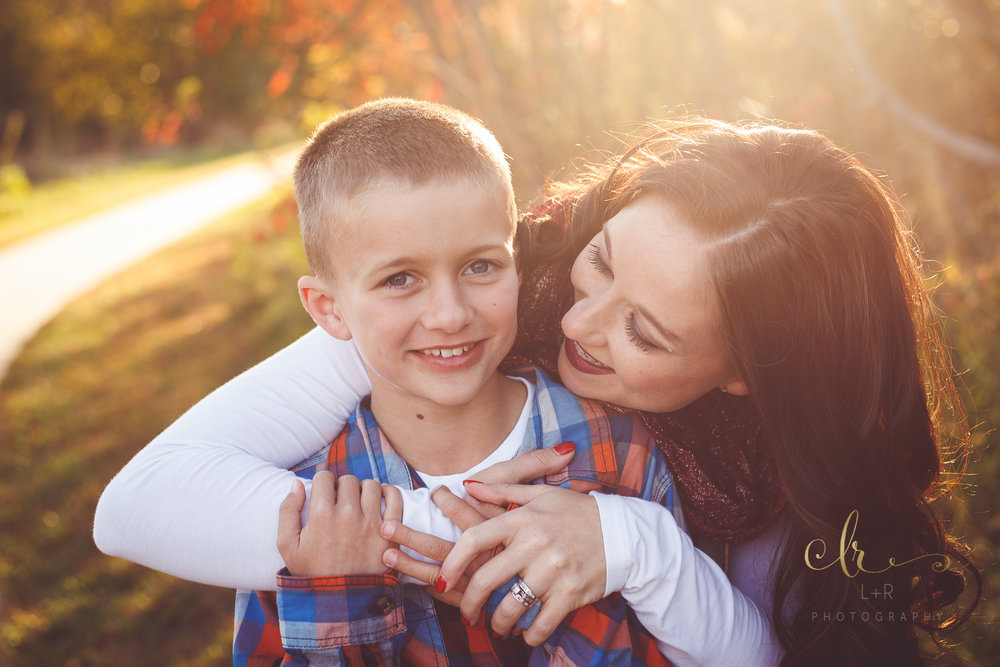 A photograph of a mother embracing her young son in the golden sunset, in an autumn family photography by L&R Photography