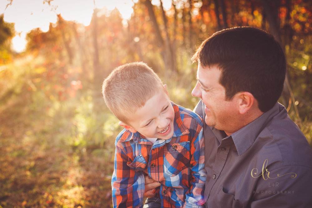 A young boy wearing read and blue flannel is right at home in his father's arms with the beautiful autumn leaves and sunset behind them - Tulsa Oklahoma Family Photography