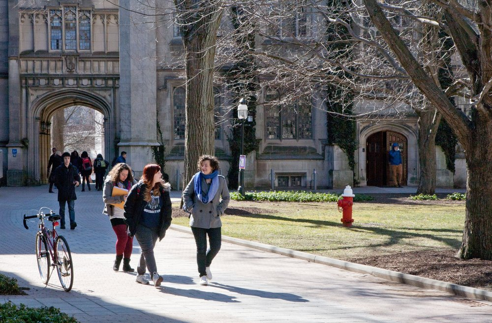 Women students walking and conversing on a sunny Princeton campus.