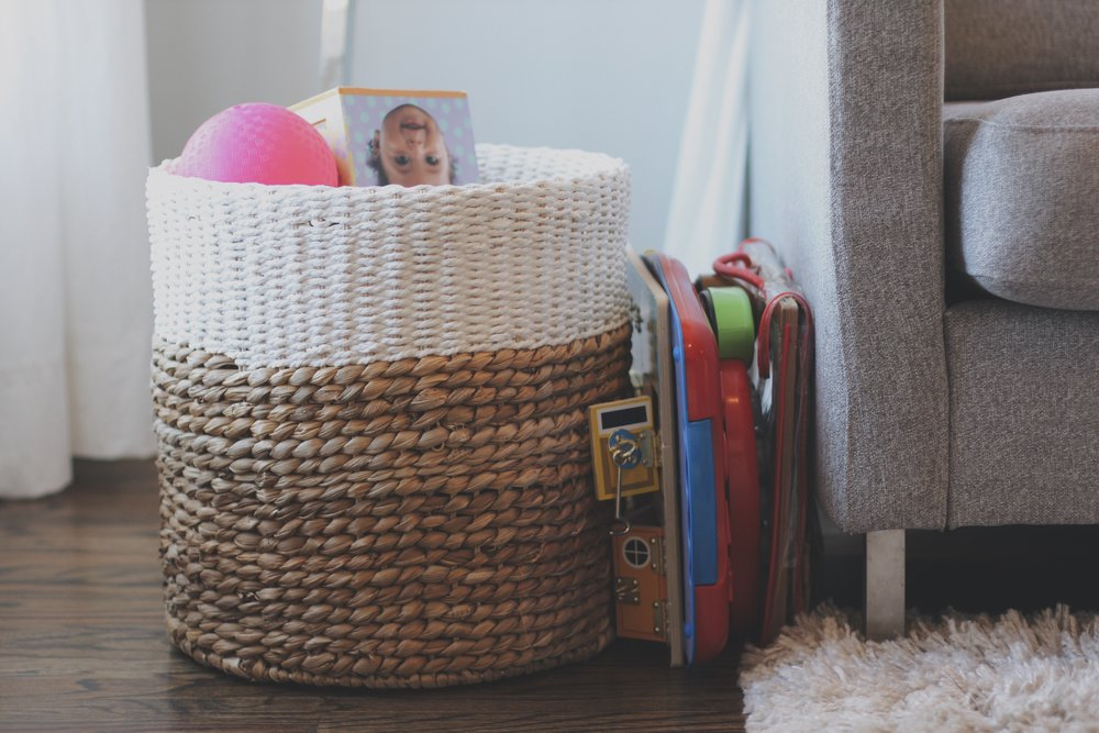 A lot of the toys go into this big basket in our living room, with a few of the bigger items seen next to it - [gasp] - hidden right underneath the couch!