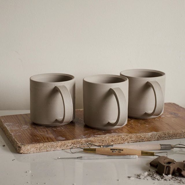 White mugs ready for bisque fire. We're really looking forward to glazing these ones in the white on white scheme! ☁️